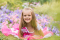 Five-year girl in a beautiful dress in a bed of flowers Royalty Free Stock Photo