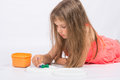 Five year girl collects mosaic lying on floor the Royalty Free Stock Images