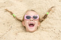 Five-year girl with glasses on a beach strewn on his head in the sand Royalty Free Stock Photo