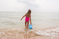 Five-year girl picking up a bucket of water in the sea Royalty Free Stock Photo