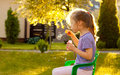 Five years old child girl child girl blowing soap bubbles outdoor caucasian in the garden at sunset Stock Image