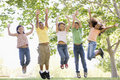 Five young friends jumping outdoors smiling Royalty Free Stock Photo