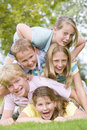 Five young friends piled on each other outdoors Royalty Free Stock Image