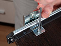 Fixing drawers installing track drawer slide rail assembling of furniture screwing screw manual screwdriver Stock Images