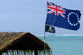Flag of the cook islands national and jolly roger pirates wave in wind at muri lagoon in rarotonga Royalty Free Stock Photo
