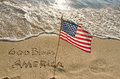Flag on the seashore american with god bless america in beach sand Royalty Free Stock Photos