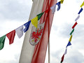 Flag of south tyrol and tibetan prayer flags with crest waving in the wind together Stock Photo