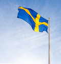 Flag of sweden against blue sky waving Royalty Free Stock Image