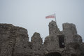 Flag on top of medieval castle ruin in heavy fog Royalty Free Stock Photo
