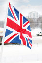Flag of united kingdom on wind at winter cloudy day in street city Stock Photos