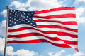 Flag of the united states of america in front bright blue sky Stock Photography