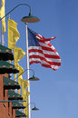 Flag and yellow banners waving by brick wall american with awnings on Royalty Free Stock Images