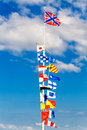 Flags on flagpole of different countries the waving in the wind against a blue sky Stock Images