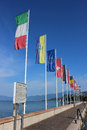 Flags flying harbor bardolino lake garda italy set of mainly country in the breeze on a sunny summer day on the wall at on itlay Royalty Free Stock Images