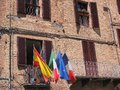 Flags on sienna balcony italy including italian and european union flying of old red brick building Royalty Free Stock Photos