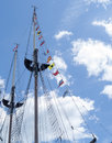 Flags on a tall ship vintage with flying off the mast against beautiful blue sky Stock Photos