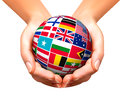Flags of the world in globe and hands. Royalty Free Stock Photo