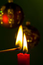 Flame of a candle the brings light into the darkness with christmas balls Stock Images