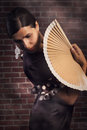 Flamenco woman with hand fan young beautiful a dancer is standing in pose looking over her shoulder red brick wall background Royalty Free Stock Photos