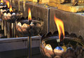 Flames of oil lamp lamps in a buddhist temple Stock Photos