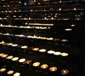 Flames of wax candles during the eucharistic celebration in the many church Royalty Free Stock Photos