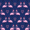 Flamingo in xmas hat with candy cane heart seamless pattern on blue polka dots background. Royalty Free Stock Photo