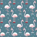 Flamingo in Christmas hat seamless pattern on blue background. Exotic New Year background. Christmas design for fabric, wallpaper,