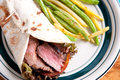 Flank steak burrito home made flatbread with garlic fried str on string beans Royalty Free Stock Photo
