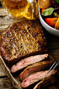Flank steak with tomato salad and glass of beer style vintage selective focus top view Royalty Free Stock Photography