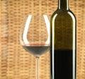 Flasche und Glas Weinflechtweidenhintergrund Stockfotos
