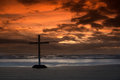 Flat beach cross black on a as the sun goes behind some clouds Royalty Free Stock Image