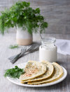 Flat bread with herbs kutaby traditional azerbaijani dish on a white plate and on a wooden table Stock Photos