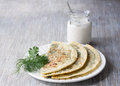Flat bread with herbs kutaby traditional azerbaijani dish on a white plate and on a wooden table Royalty Free Stock Photo