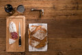 Flat lay above view of dry sausage delicatessen sliced meat with wine and traditional bread on wooden board Royalty Free Stock Photo