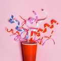 Flat lay of Celebration. Paper cup with colorful party streamers