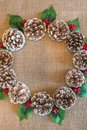Flat lay Christmas wreath of pinecones, red berries, and holly leaves Royalty Free Stock Photo