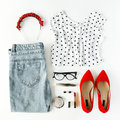 Flat lay feminine clothes and accessories collage with shirt, jeans, glasses, mascara, lipstick, red high heel shoes, earrings and Royalty Free Stock Photo
