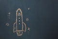 Flat lay Handmade drawing rocket ship launch / take off to the space with star on the blackboard by chalk board. Royalty Free Stock Photo