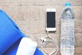 Flat lay of mobile phone with earphones, water bottle, towel and blue yoga mat Royalty Free Stock Photo