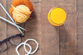 Flat lay of orange juice in glass, yarn and knitting with woman accessories on wood Royalty Free Stock Photo