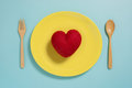 Flat lay of red heart on yellow plate with fork on pastel blue color background