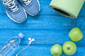 Flat lay sport shoes, bottle of water, mat and earphones on blue Royalty Free Stock Photo