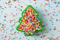 Flat lay view of Christmas tree shaped cookie cutter filled with rainbow sugar sprinkles. Royalty Free Stock Photo