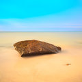 Flat rock on a golden beach. Long exposure. Stock Images