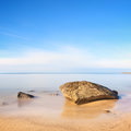 Flat rock on golden beach and sea. Long exposure. Stock Photos