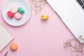 Flatlay of laptop, cake macaron and cup of tea on pink table. Be Royalty Free Stock Photo