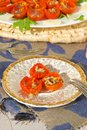 Flavorful healthy starter oven baked cherry tomatoes with oregano and fresh chopped garlic on an old porcelain plate Stock Photo