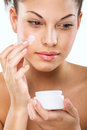 Flawless-skinned woman with moisturizing face cream Royalty Free Stock Photo