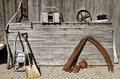 Flea market items for sale old antique rusty at a include a shovel scythes pulley and an weathered door Stock Photo