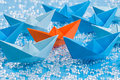 Fleet of blue origami paper ships on blue water like background surrounding an orange one waterlike in the middle Royalty Free Stock Images